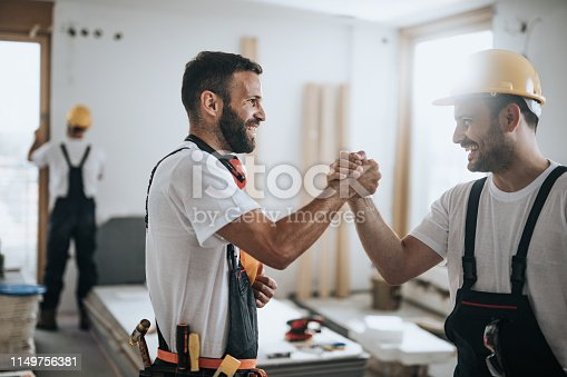 961745166istockphoto Happy construction workers greeting each other at construction site. 1149756381