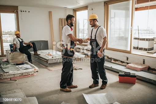 961745166istockphoto Happy construction workers shaking hands at construction site. 1094819070