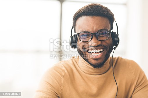 Helpline Concept. Head shot of smiling black man wearing headset at office looking at camera. Empty space