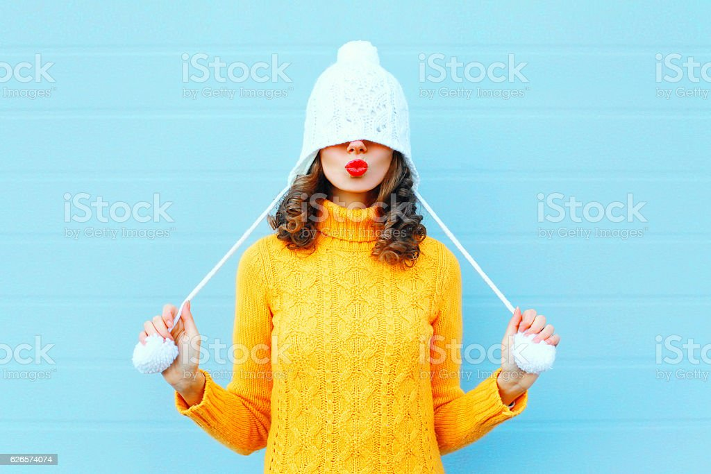 Happy cool girl blowing red lips makes air kiss stock photo