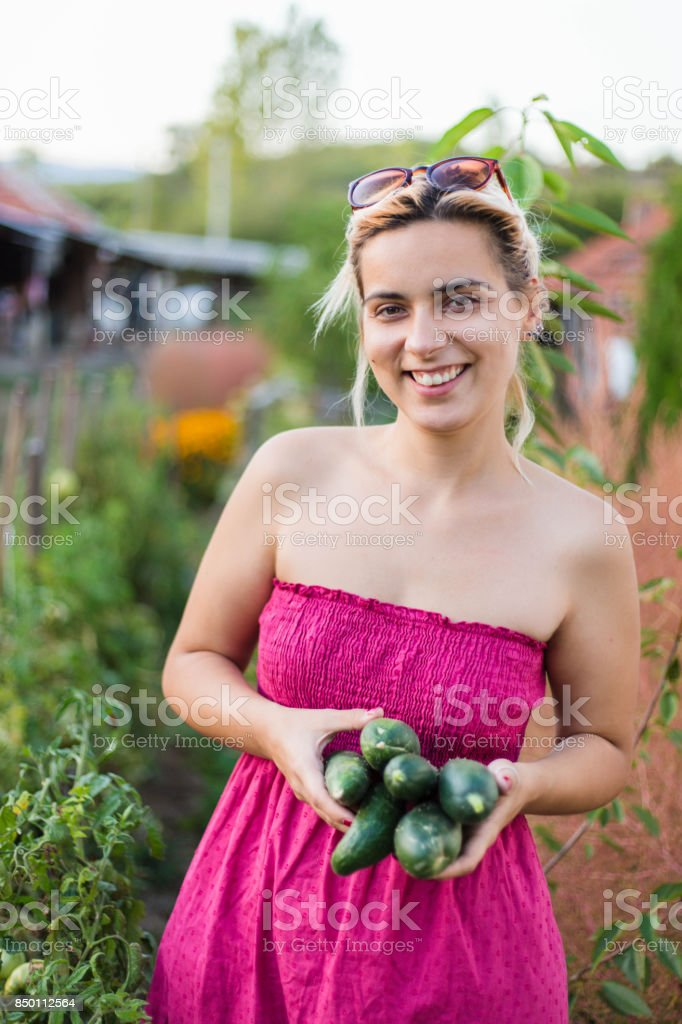 Happy countrywoman holding vegetables stock photo