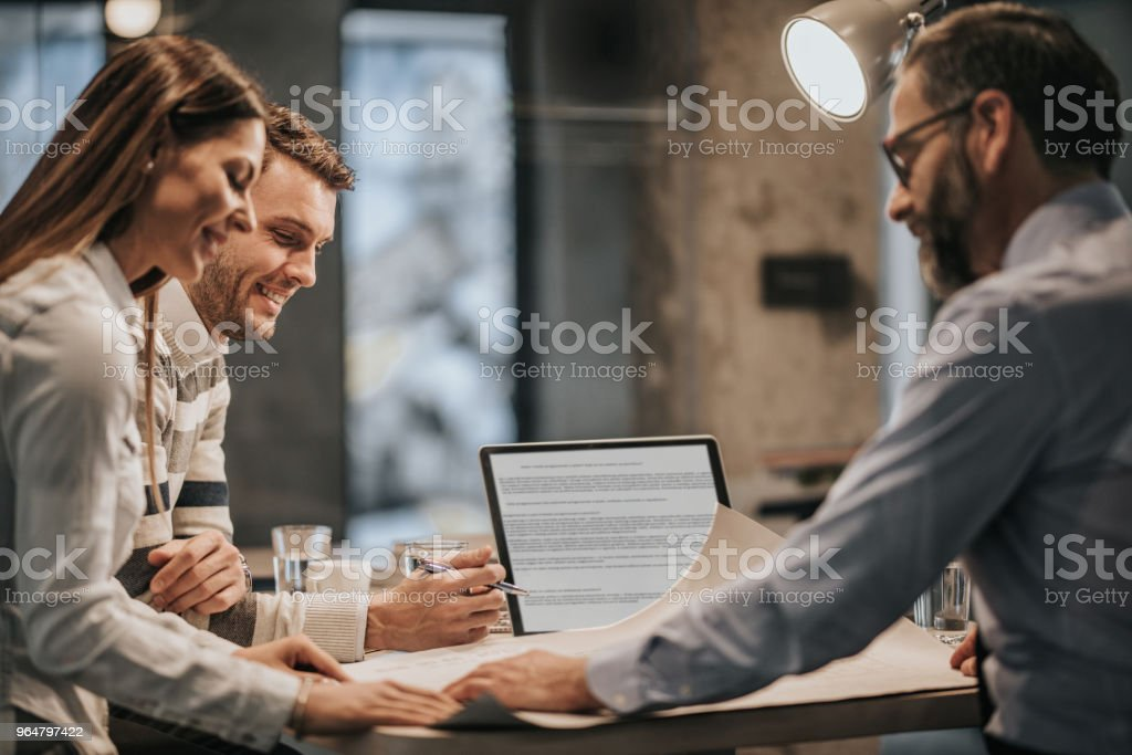 Happy couple analyzing blueprints with real estate agent in the office. royalty-free stock photo