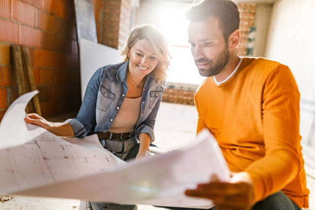 Happy couple analyzing plans at their renovating apartment. stock photo
