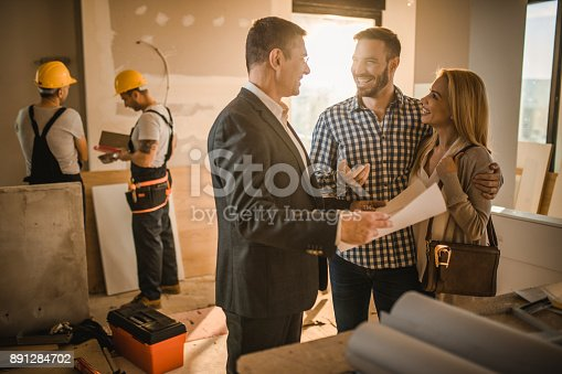 istock Happy couple and building contractor talking about housing plan at construction site. 891284702