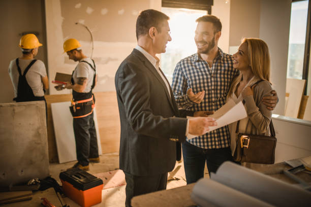 Happy couple and building contractor talking about housing plan at construction site. stock photo