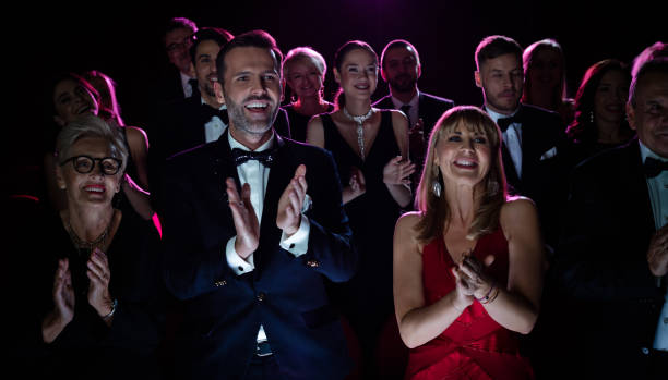 Happy couple applauding while watching opera Mature couple giving standing ovation while watching opera. Happy crowd enjoying performance during weekend. They are in elegant wear. evening wear stock pictures, royalty-free photos & images