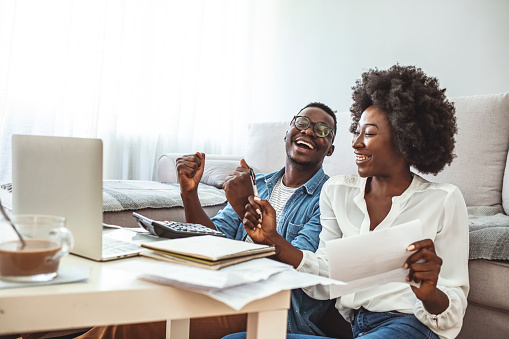 Photo of cheerful loving young couple using laptop and analyzing their finances with documents. Look at papers. Happy couple at home paying bills with laptop