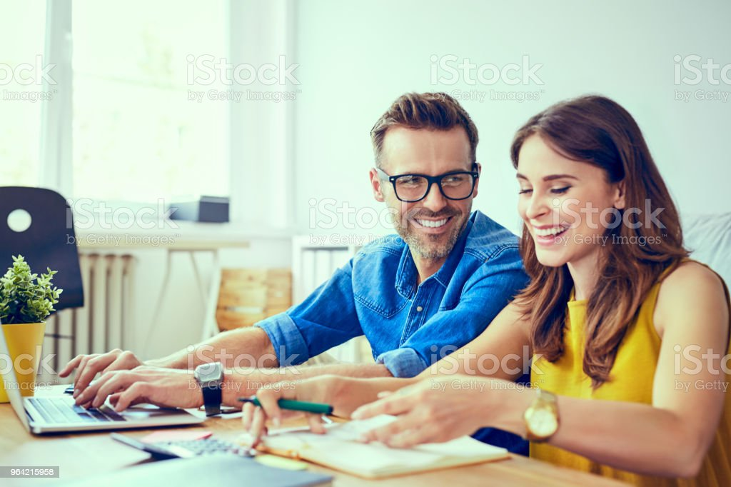 Happy couple at home paying bills with laptop stock photo