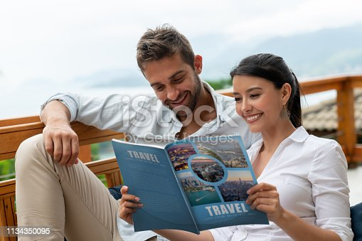 Happy couple at home reading a travel magazine