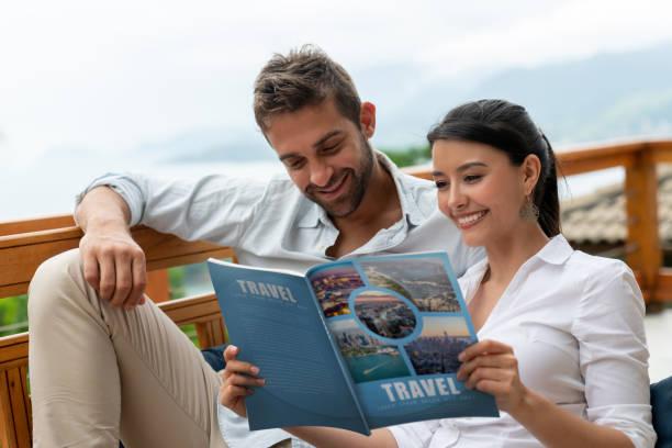 Glückliches Paar zu Hause beim Lesen eines Reisemagazins – Foto