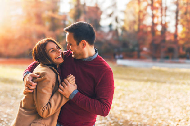 Happy couple at public park in autumn Couple in love hugging and enjoying at public park in autumn romantic activity stock pictures, royalty-free photos & images