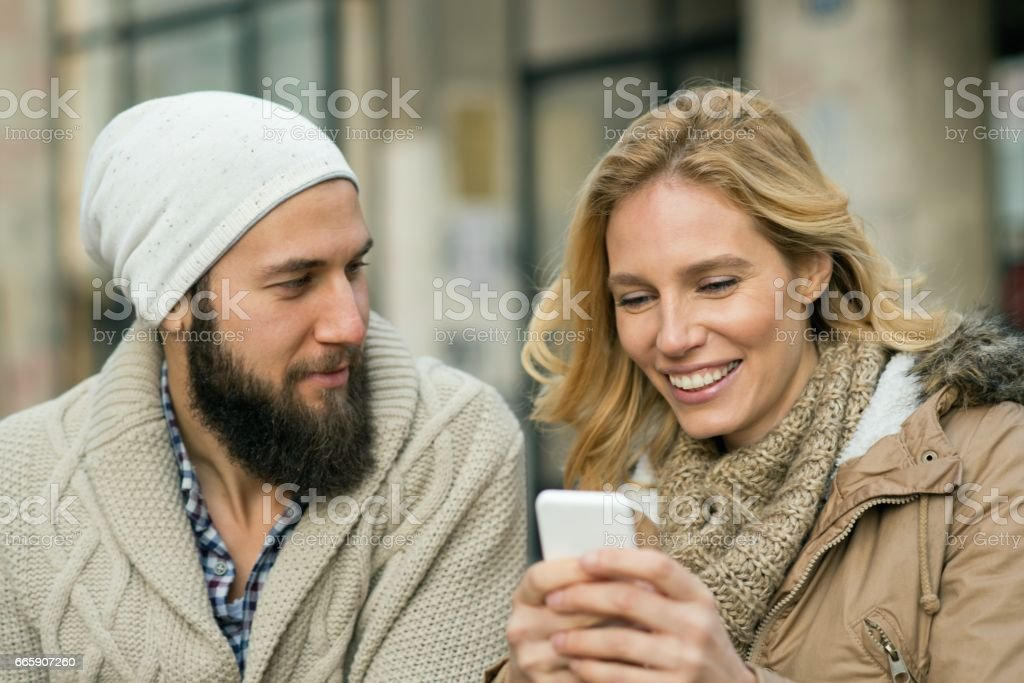 Happy couple at the bar using mobile phone foto stock royalty-free