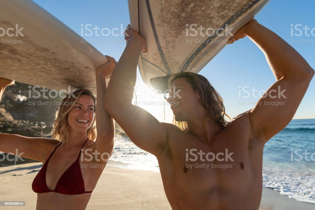 Happy couple at the beach having fun surfing - Royalty-free Adult Stock Photo