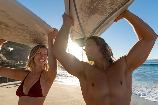Happy Couple At The Beach Having Fun Surfing Stock Photo - Download Image Now