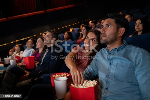 Portrait of a happy couple at the movies and woman stealing popcorn from her boyfriend - entertainment concepts