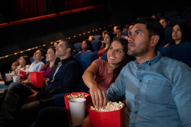 Glückliches Paar bei den Filmen und Frau stehlen Popcorn – Foto