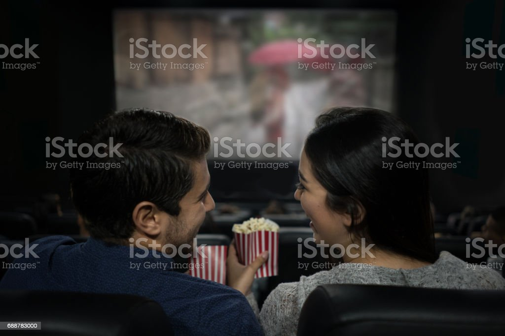 Happy couple at the movies eating popcorn and having fun stock photo