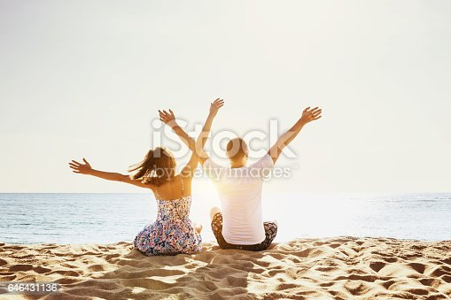 Happy couple having fun on background of sunset beach. Sea vacations concept. Space for text