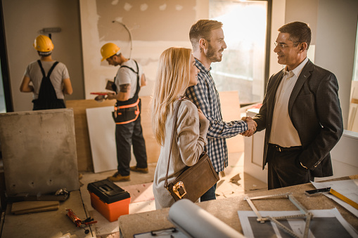 istock Happy couple came to an agreement with building contractor. 936385290