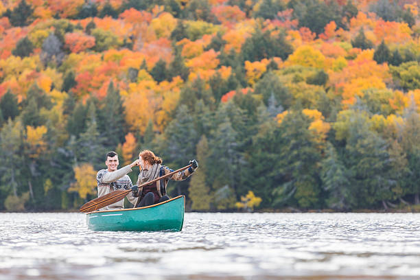 happy couple canoeing in a lake in canada - canada travel stock photos and pictures