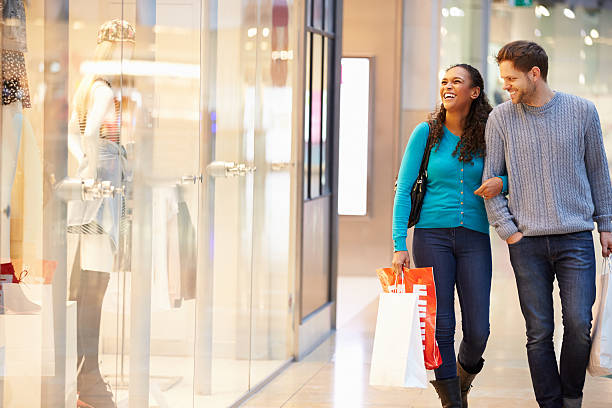 Happy Couple Carrying Bags In Shopping Mall stock photo