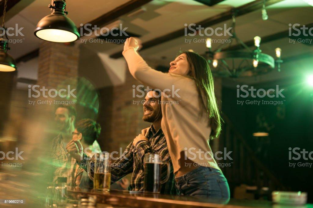 Casal feliz celebrando enquanto assistia a um jogo de futebol em um bar. - foto de acervo