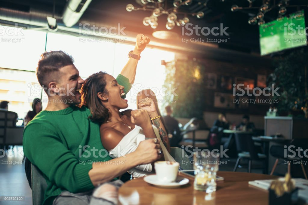 Happy couple celebrating while watching a football game in a cafe stock photo