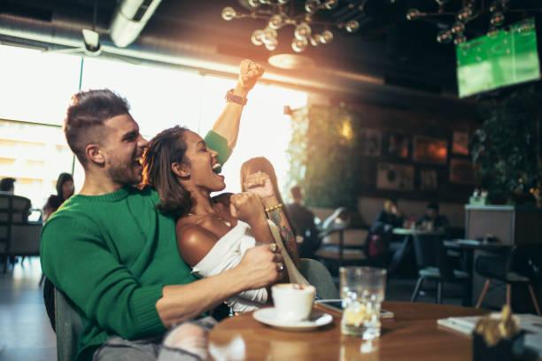 Casal feliz celebrando enquanto assistia a um jogo de futebol em um café - foto de acervo