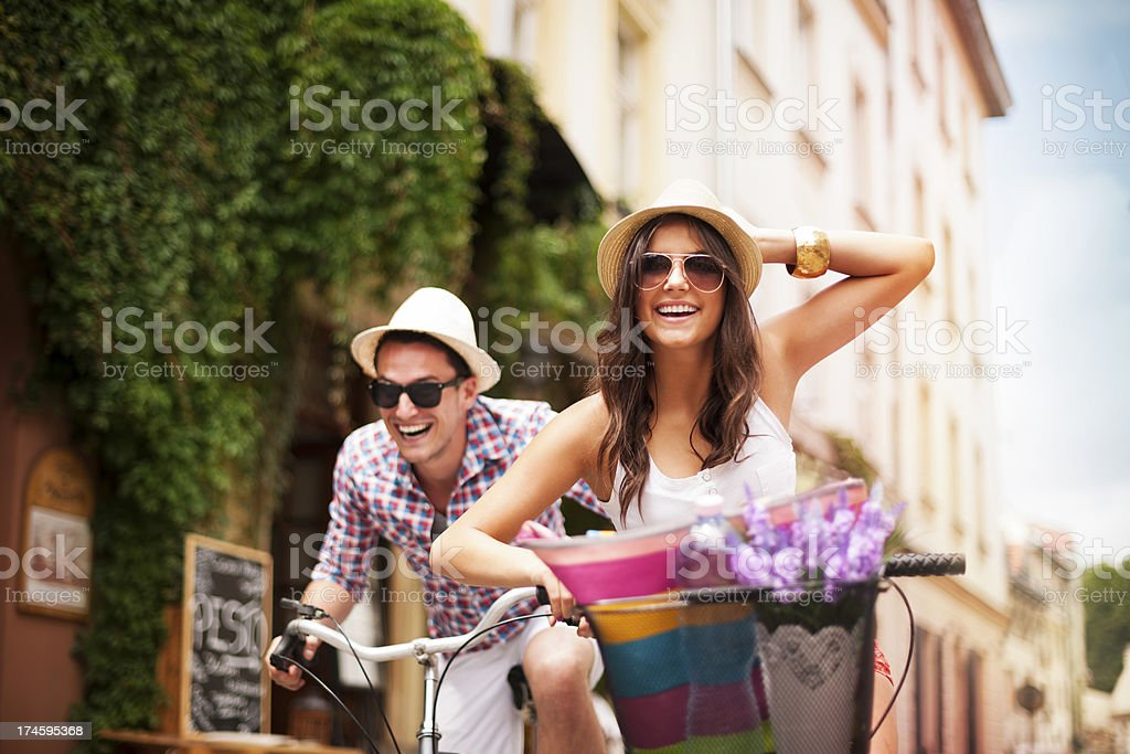 Happy couple chasing each other on bike stock photo