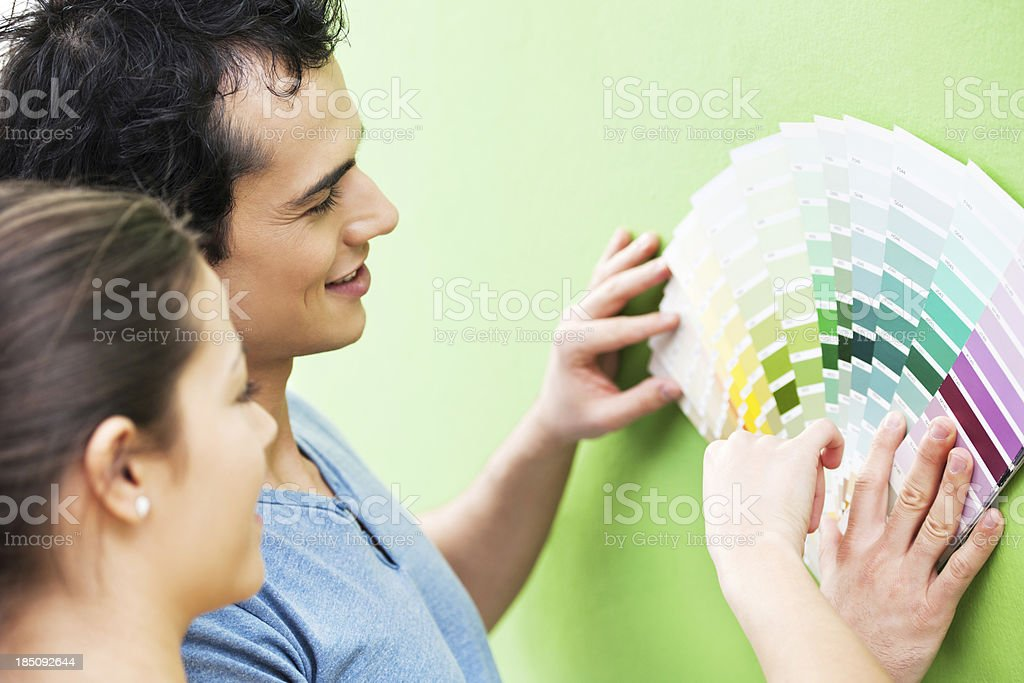 Happy couple choosing color for the wall stock photo