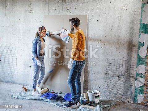 Young happy couple talking while choosing colors from color swatch while renovating their apartment. Copy space.