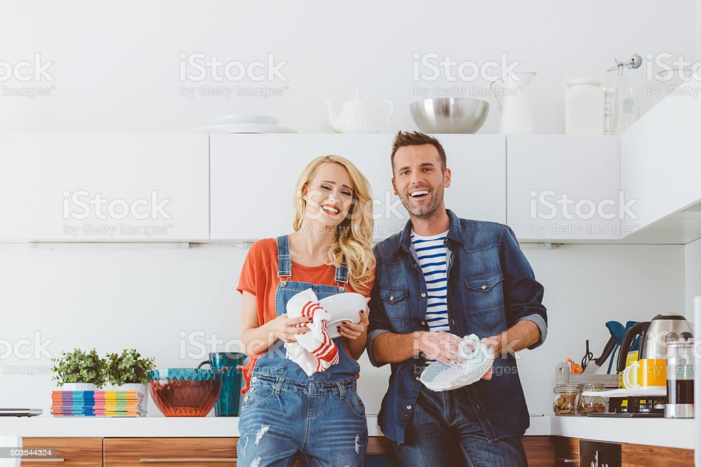 Happy couple cleaning dishes in the kitchen stock photo