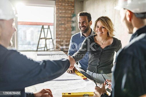 Happy couple came to an agreement with their building contractors at construction site. Focus is on woman.