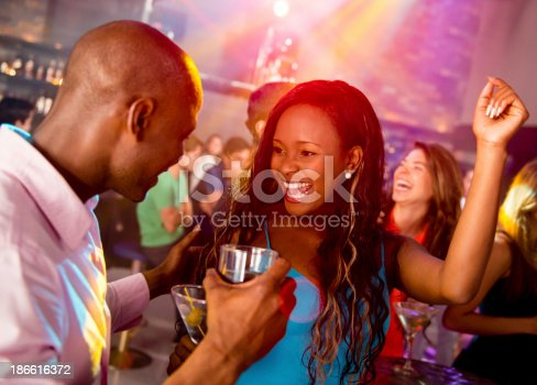 Happy couple clubbing at a nightclub having fun dancing
