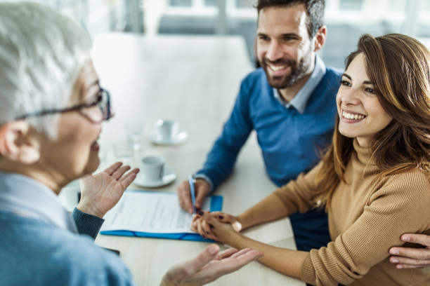 happy couple communicating with their financial advisor on a meeting in the office. - financial advisor with clients stock photos and pictures