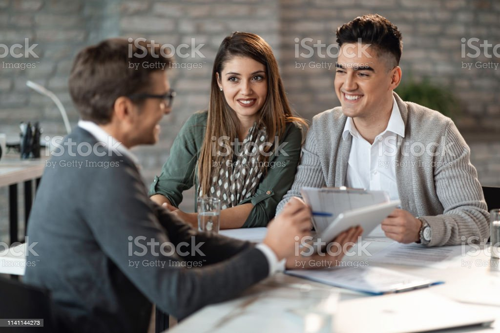 Young happy couple talking to their financial consultant on a meeting...