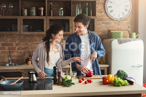 Happy couple cooking dinner together in their loft kitchen at home. Man preparing vegetable salad for his girlfriend, copy space