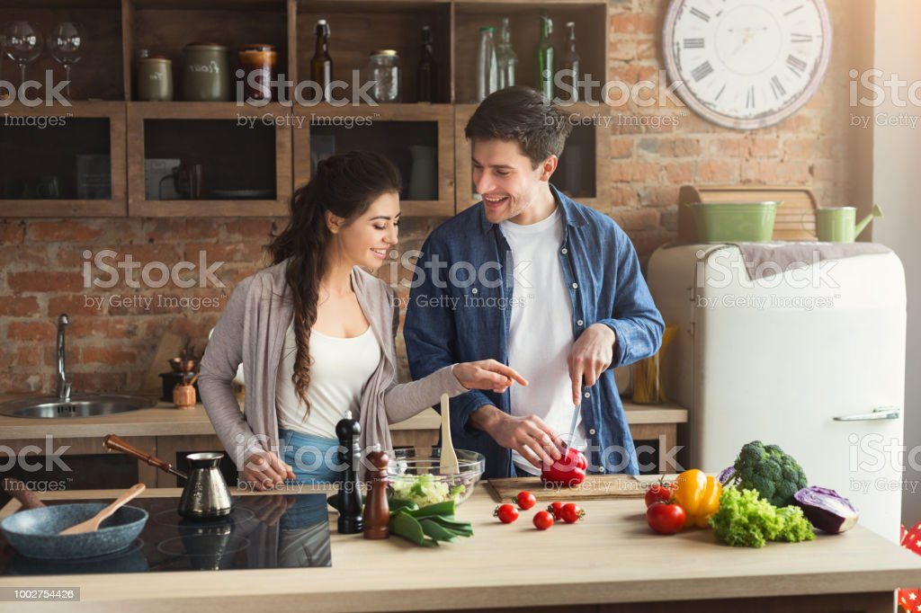 Happy couple cooking dinner together stock photo