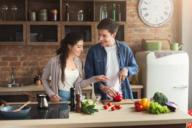 Happy couple cooking dinner together Happy couple cooking dinner together in their loft kitchen at home. Man preparing vegetable salad for his girlfriend, copy space preparing food stock pictures, royalty-free photos & images