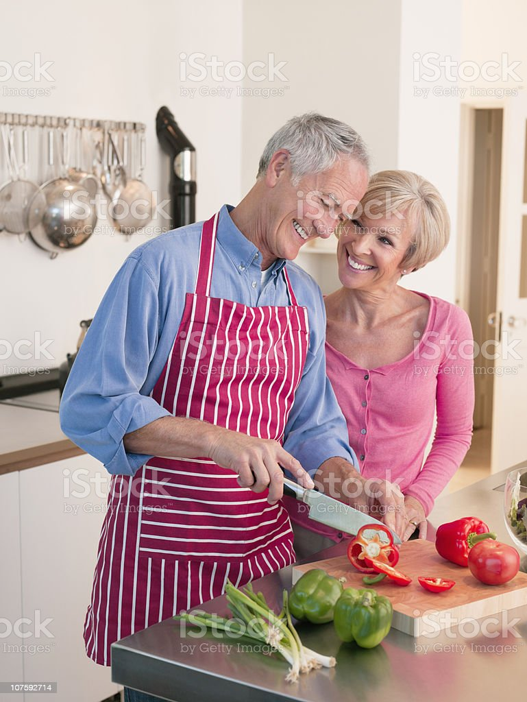 Happy couple cutting vegetables in kitchen royalty-free stock photo