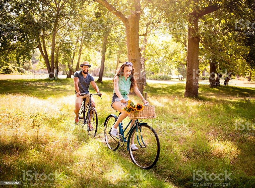 Happy couple cycling together in summer in a park stock photo