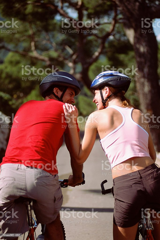 Happy couple cycling together royalty free stockfoto