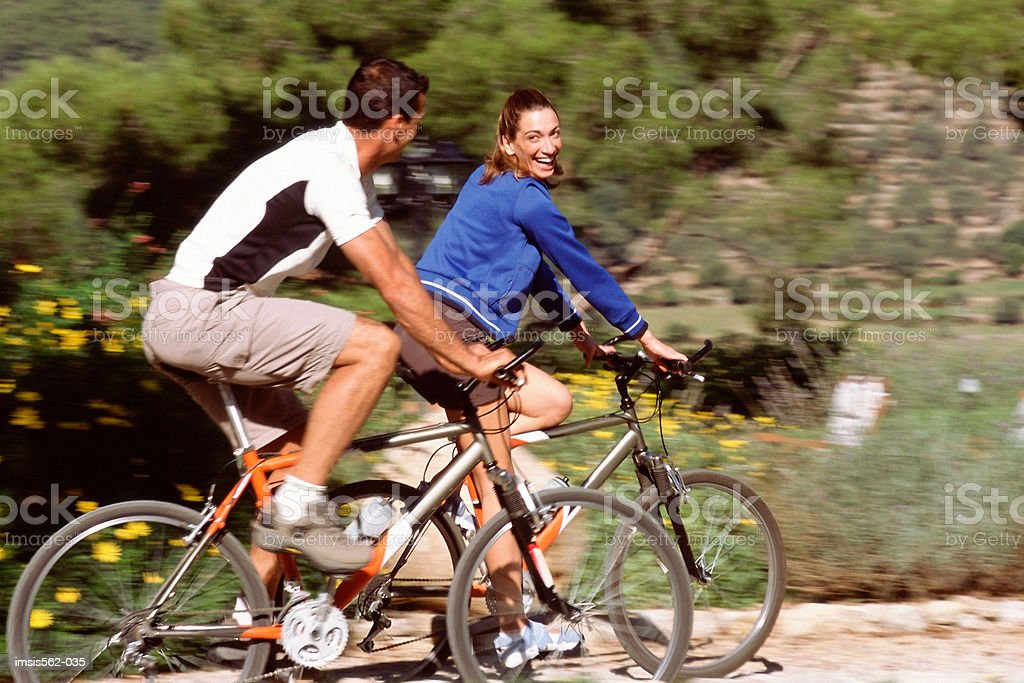 Happy couple cycling together royalty-free stock photo