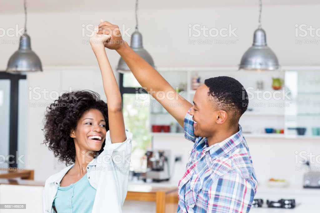 Happy couple dancing in kitchen stock photo