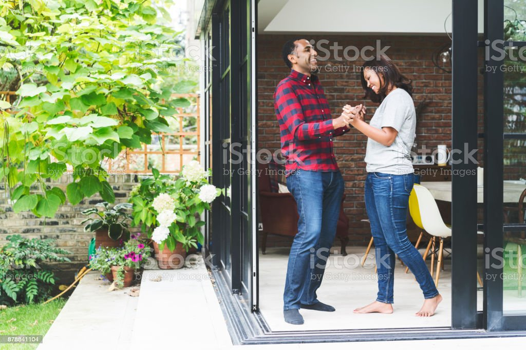 Happy couple dancing in kitchen seen from doorway stock photo