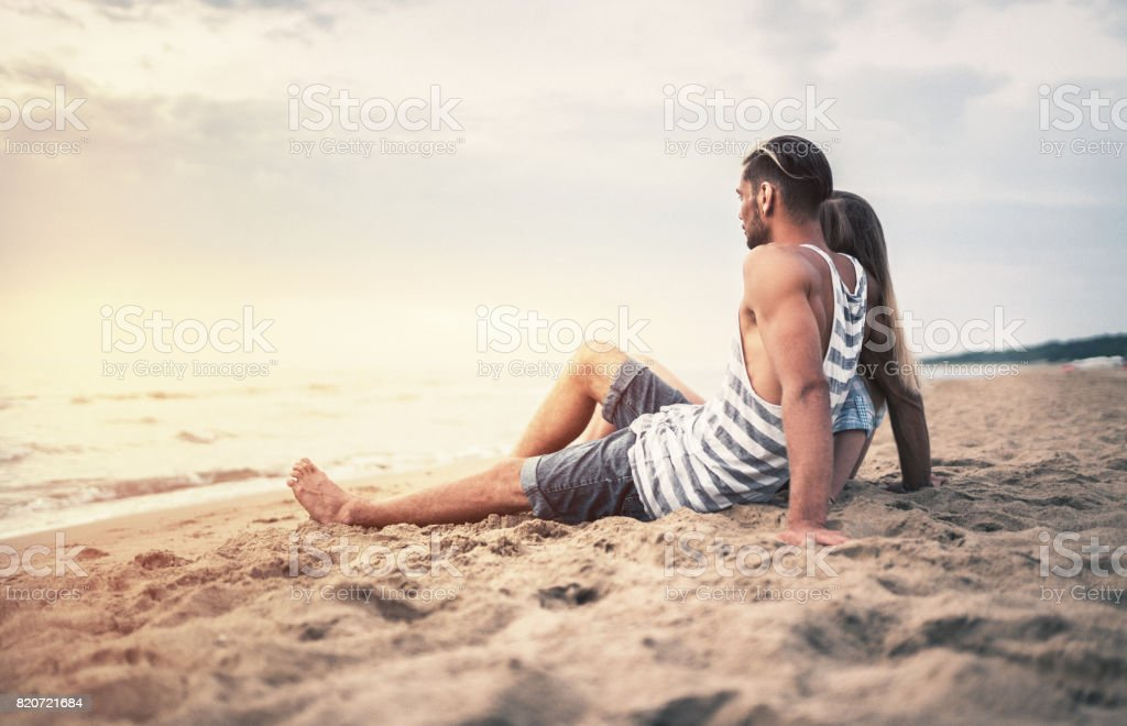 Happy couple date at the seaside at sunset stock photo
