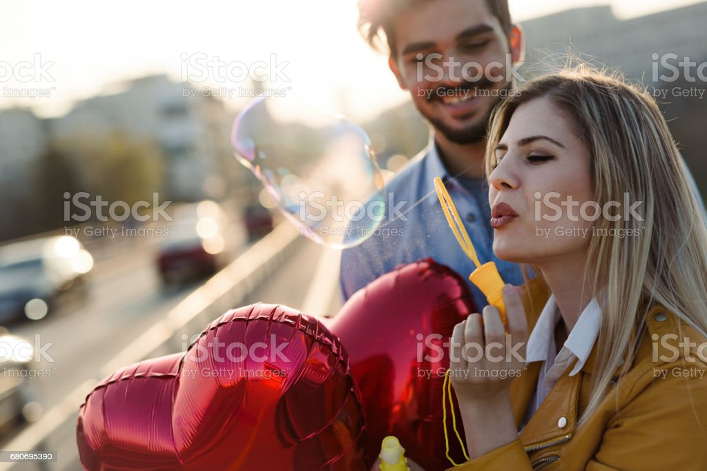 Happy couple dating and smiling while blowing bubbles stock photo