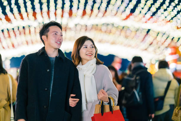 Happy couple dating at night A portrait of a happy couple dating at night at a Christmas market. shopping couple asian stock pictures, royalty-free photos & images