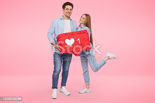 Full body young man and woman smiling and holding speech bubble with like icon while dating in social media app against pink background