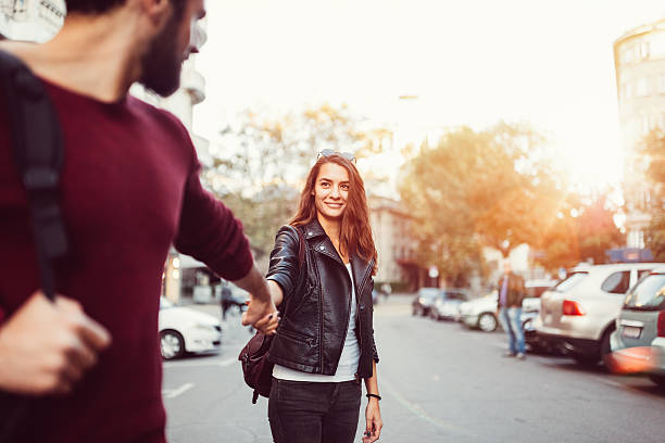 Happy couple dating outside Young couple holding hands at the street temptation stock pictures, royalty-free photos & images